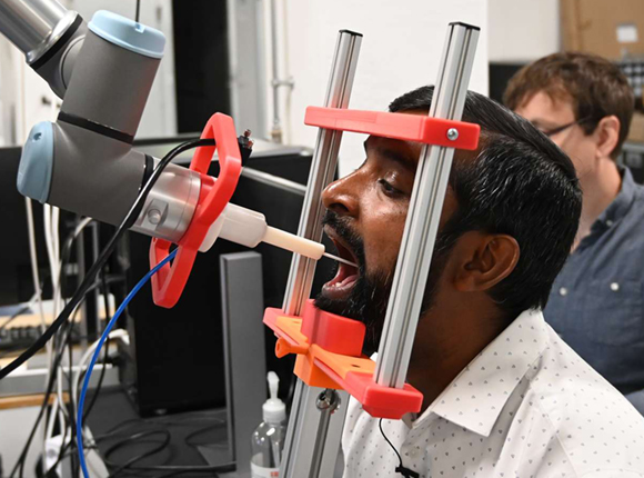 Picture of Thiusius Rajeeth Savarimuthu getting a throat swab by the world's first fully automatic robot that can carry out throat swabs for Covid-19.
