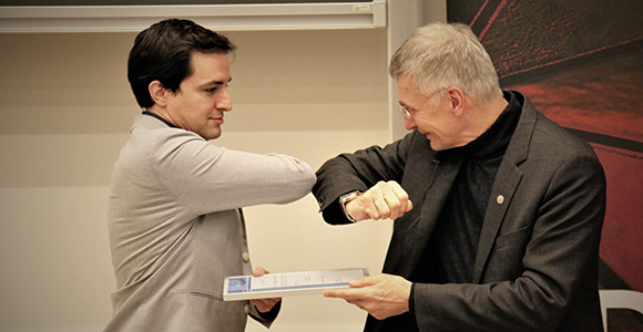 Head of the Mads Clausen Institute, Horst-Günter Rubahn, gives BHJ Young Scientist Award to Jaume Castan Pinos with 'Corona handshake'.