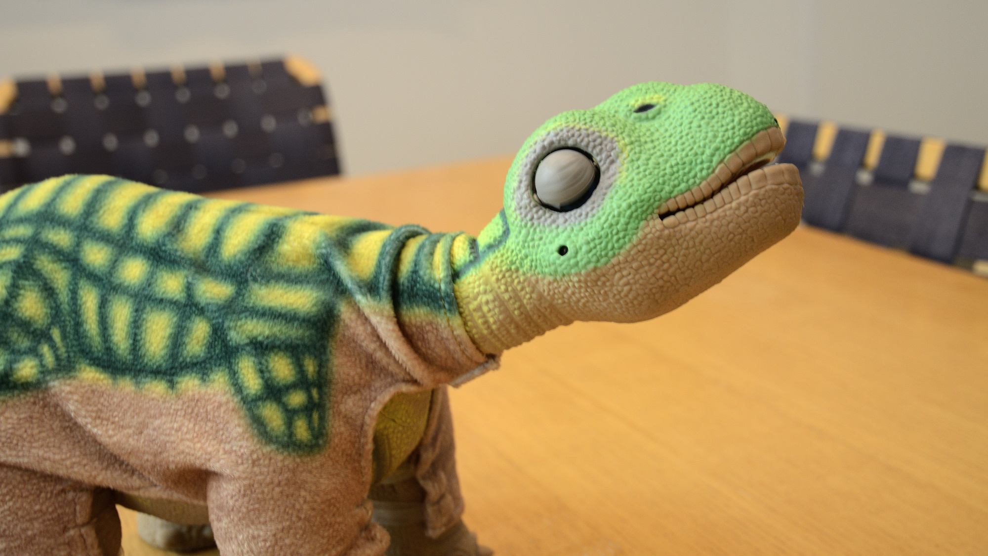 A Pleo robot comfortably stretching his body.