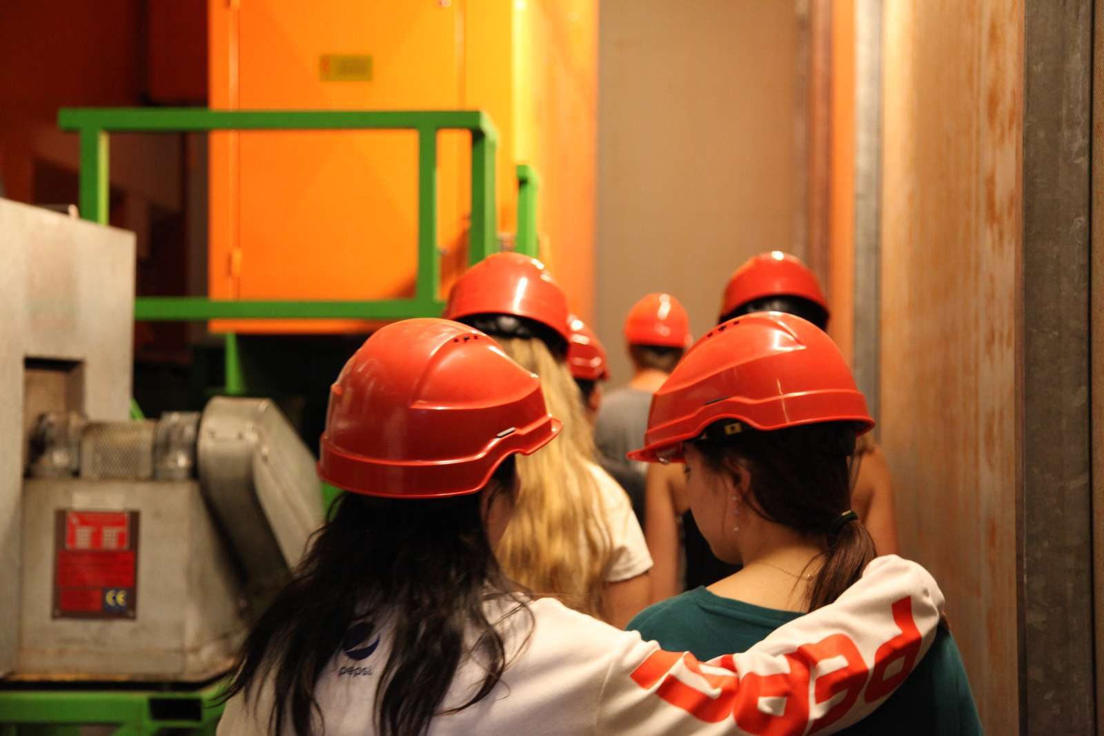 A group of students with helmets in an industrial complex, photographed from the rear. One student is hugging another student.