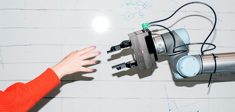 Et foto af en menneskearm og en robotarm, som rækker fingrene frem for at røre hinanden