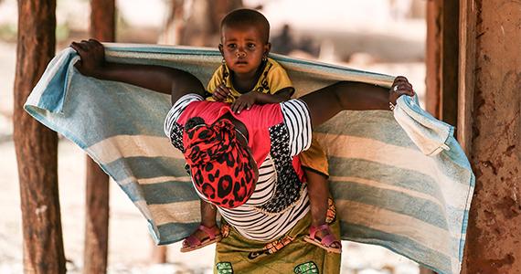 En kvinde binder en vikle om sit barn.