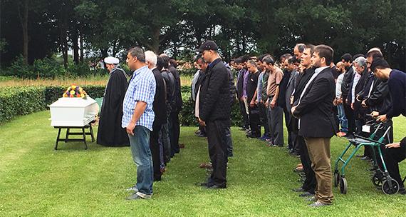 Billedet viser en stor gruppe mænd til begravelse.
