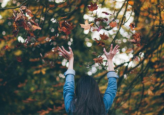 Billedet viser en kvinde bagfra, som kaster blade op i luften.