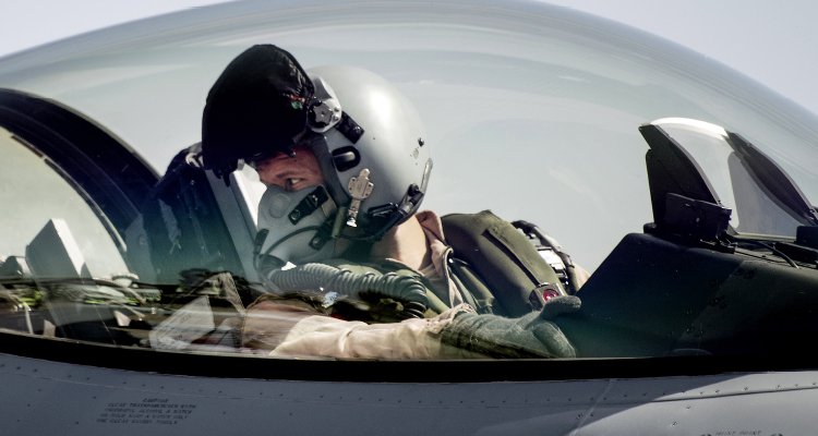 Billedet viser en pilot i cockpittet på et kampfly.